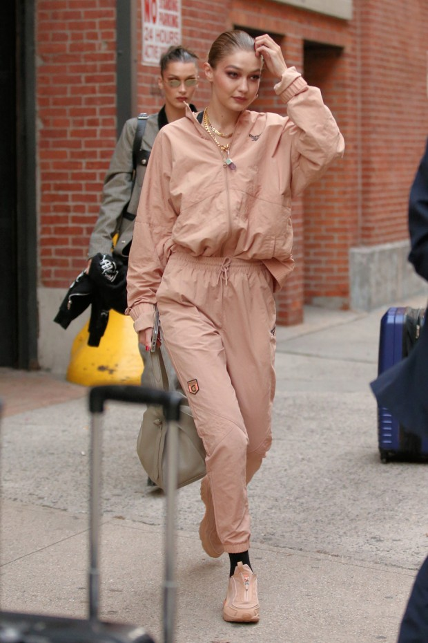 Models Bella Hadid And Gigi Hadid, Wearing A Faded Orange Reebok Sweatsuit, Leave Highline Stages In New York City
